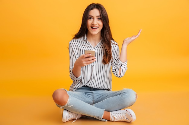 Retrato de una joven excitada con teléfono móvil