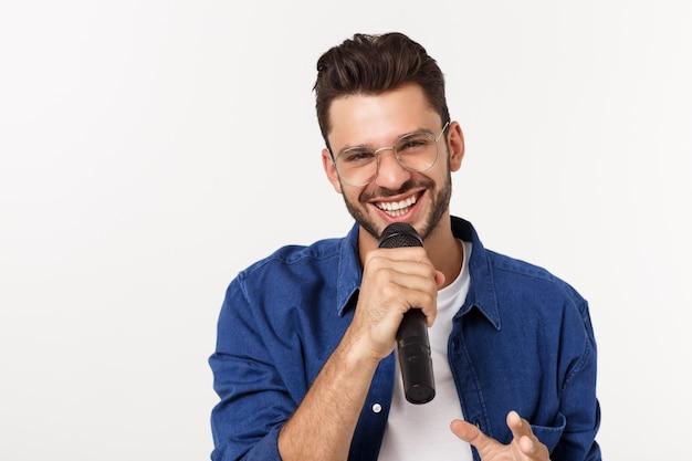 Retrato de un joven excitado en camiseta aislado sobre fondo gris, cantando.