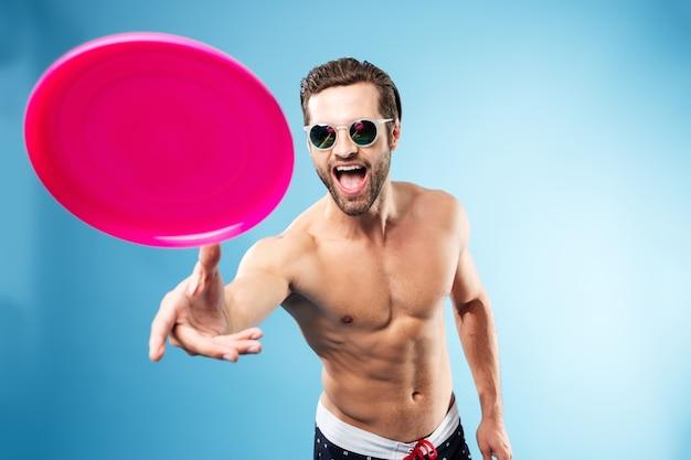 Retrato de un joven excitado en pantalones cortos de verano jugando