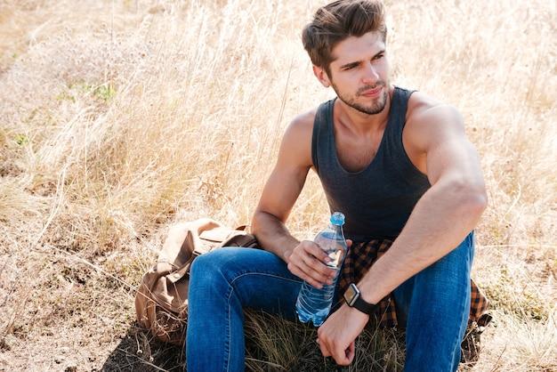 Retrato de un joven excursionista con mochila descansando y bebiendo agua