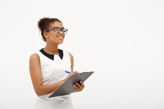 Retrato de joven exitosa mujer de negocios africanos en blanco
