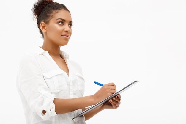 Retrato de joven exitosa mujer de negocios africanos sobre pared blanca