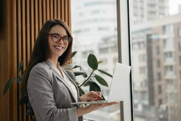 Retrato de joven exitoso gerente usando laptop, trabajando en la oficina
