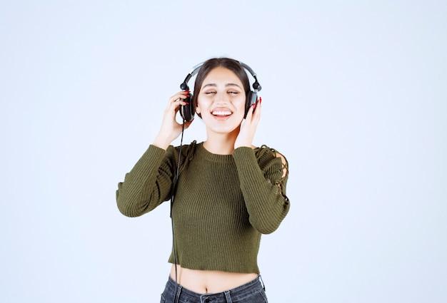 Retrato de joven expresiva escuchando música sobre fondo blanco.