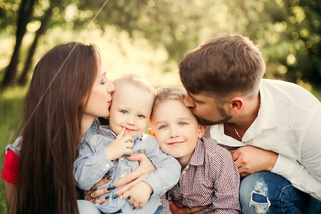 Retrato de joven familia feliz besando a su pequeño hijo.