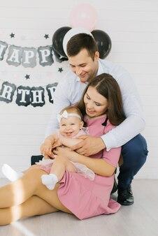 Retrato de una joven familia con una niña de un año en sus brazos. primer cumpleaños del bebé