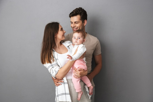 Retrato de una joven familia sonriente con su pequeña niña
