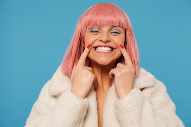 Retrato de joven feliz atractiva dama de cabello rosa con maquillaje de color manteniendo los dedos índices en las comisuras de la boca mientras sonríe ampliamente, vistiendo un abrigo de piel sintética blanca