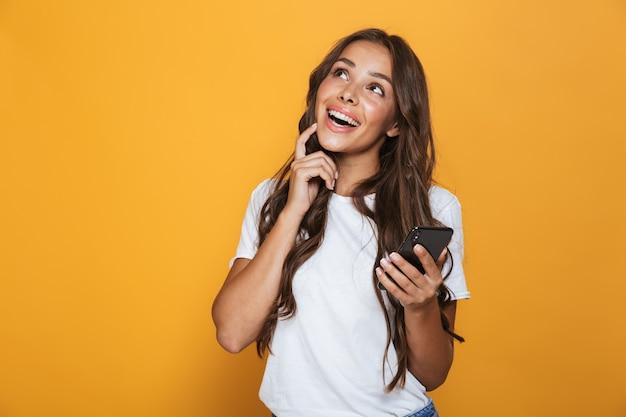 Retrato de una joven feliz con cabello largo morena de pie sobre la pared amarilla, sosteniendo el teléfono móvil, mirando a otro lado