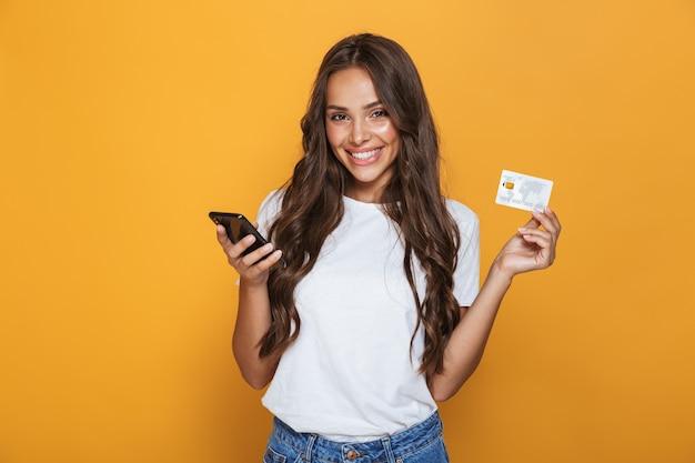 Retrato de una joven feliz con cabello largo morena de pie sobre una pared amarilla, sosteniendo un teléfono móvil, mostrando una tarjeta de crédito de plástico
