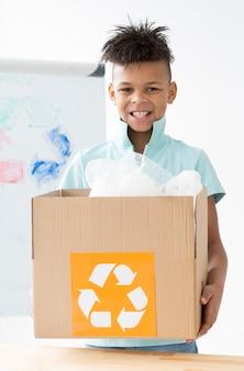 Retrato de joven feliz con caja de reciclaje
