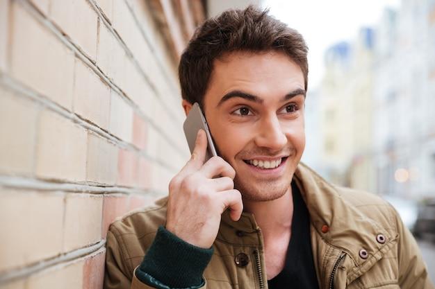 Retrato de joven feliz caminando por la calle y mirando a un lado mientras habla por su teléfono.
