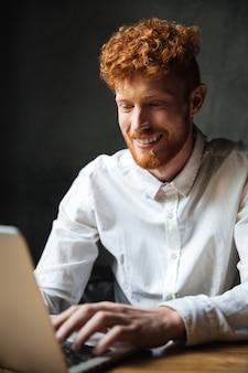 Retrato de un joven feliz escribiendo en una computadora portátil