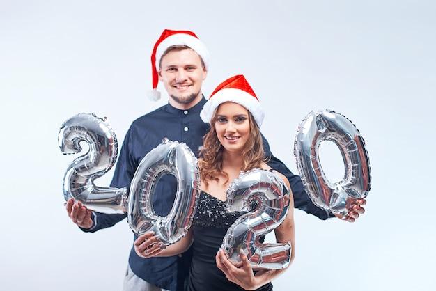 Retrato de joven feliz hombre y mujer con sombreros rojos de santa con globos metálicos 2020.