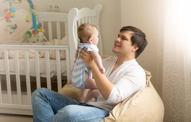 Retrato de joven feliz jugando con su bebé en el dormitorio