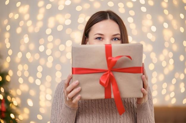 Retrato de joven feliz labios rojos escondidos detrás de la caja de regalo envuelta.