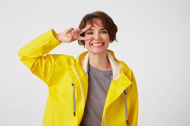Retrato de joven feliz linda chica de pelo corto lleva capa de lluvia amarilla, sonríe ampliamente y mira a la cámara a través de un gesto de paz, toca la mejilla, se para sobre la pared blanca.