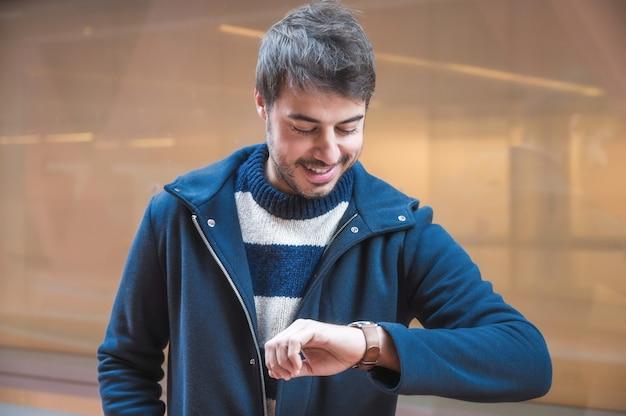 Retrato de joven feliz mirando su reloj. fondo urbano