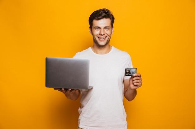 Retrato de un joven feliz con ordenador portátil