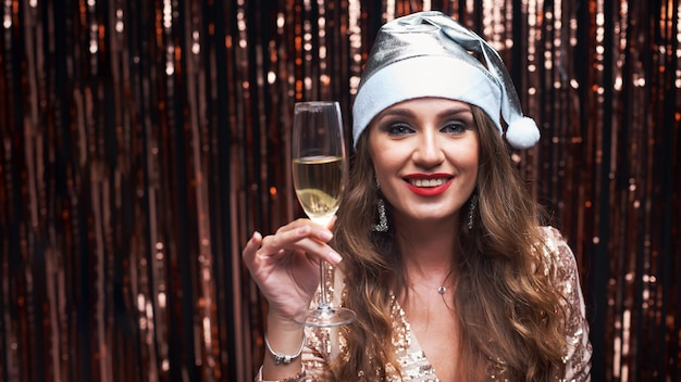 Retrato de joven feliz en plata santa sombrero con copa de champán en las manos.