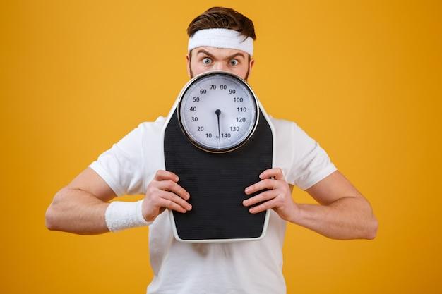Retrato de un joven fitness hombre escondido detrás de las básculas
