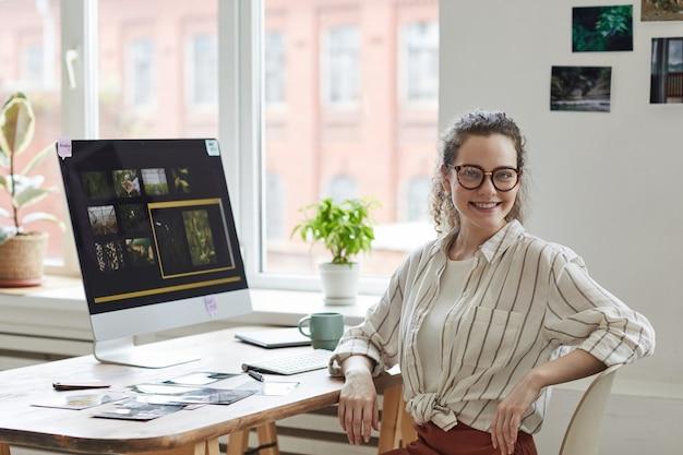 Retrato de joven fotógrafa sonriendo a la cámara mientras posa en el escritorio con software de edición de fotos en la pantalla de la computadora, espacio de copia