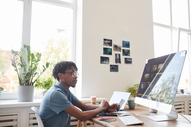 Retrato de joven fotógrafo afroamericano con computadora en el escritorio en la oficina en casa con software de edición de fotos en pantalla, espacio de copia