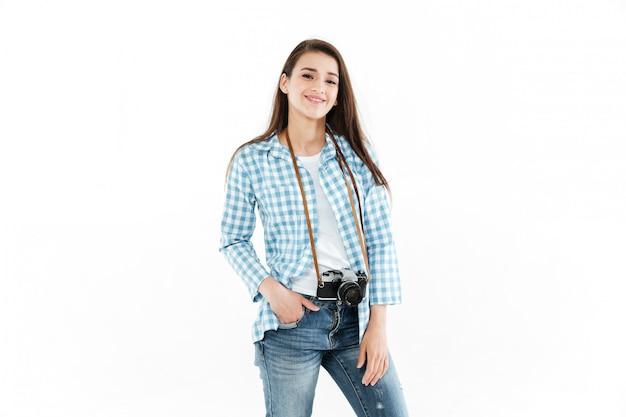 Retrato de un joven fotógrafo feliz de pie con cámara retro