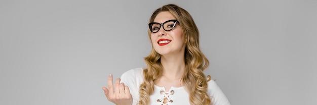 Retrato de una joven en gafas y una blusa blanca sobre un fondo gris