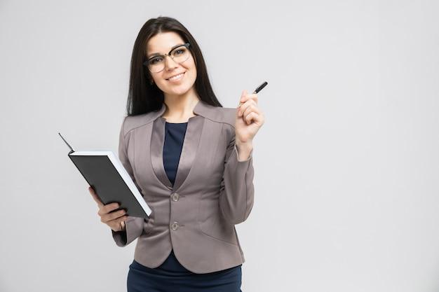 Retrato de una joven con gafas con un diario en sus manos aislado una luz