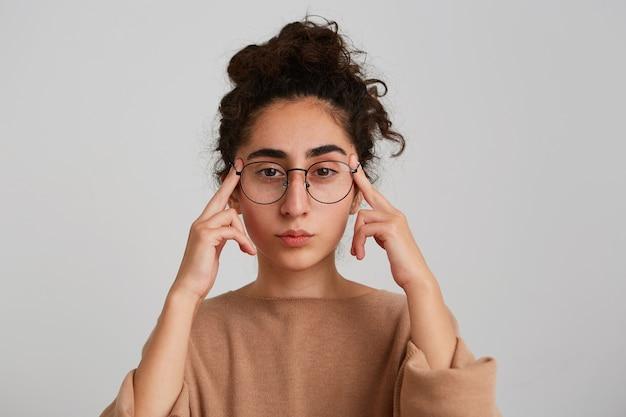 Retrato de joven georgiana pensativa concentrada con pelo rizado viste jersey beige y gafas tocando sus sienes y pensando aislado sobre pared blanca