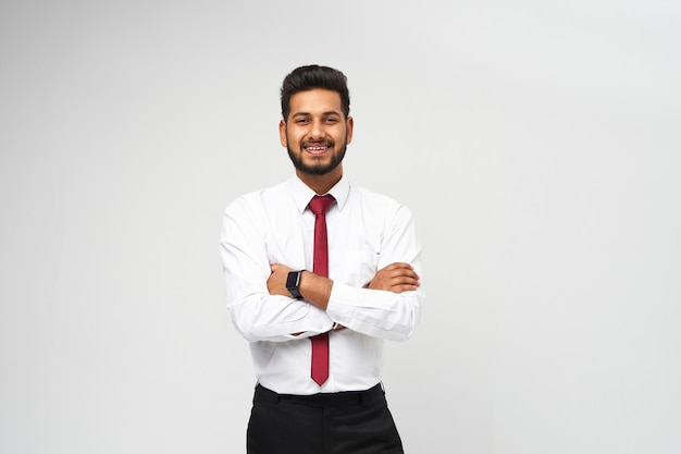 Retrato de joven gerente indio en camiseta y corbata de brazos cruzados y sonriendo en la pared blanca aislada