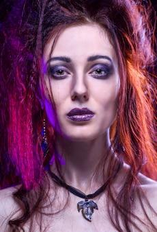 Retrato de joven gótica sexy con el pelo largo sobre fondo oscuro en estudio