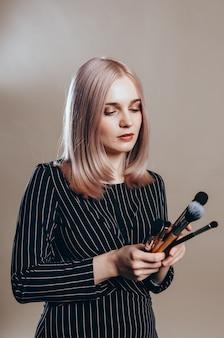 Retrato de una joven guapa con pinceles de maquillaje