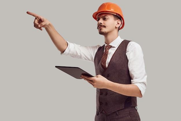 Retrato de joven y guapo arquitecto árabe confiado con bigote elegante en traje de lana y casco de construcción tiene tableta