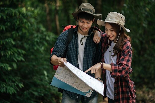 Retrato joven guapo asiático con mochila y sombrero de trekking y novia bonita de pie y comprobando la dirección en el mapa de papel mientras camina por el sendero del bosque, concepto de viaje con mochila