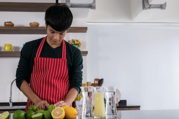Retrato de joven guapo asiático sonriendo y de pie jugo de limón exprimido en una cocina moderna.