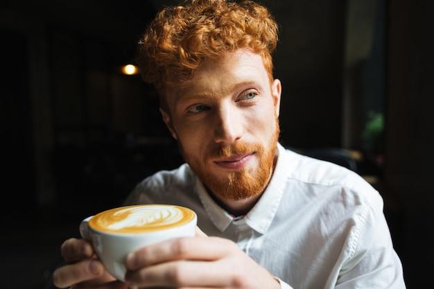 Retrato de joven guapo con barba pelirroja en camisa blanca con taza de café, mirando a un lado