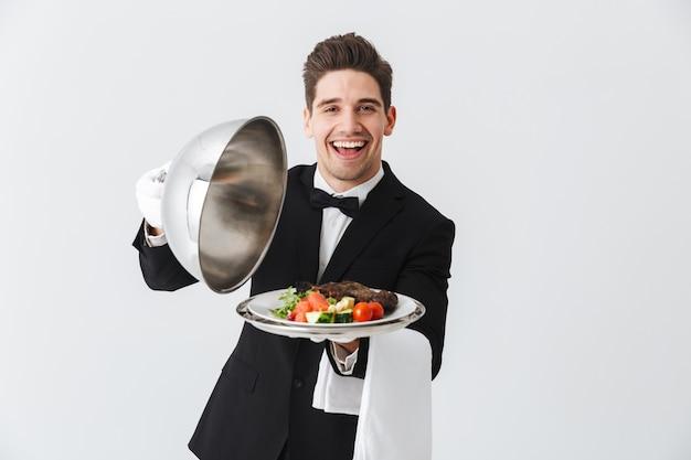Retrato de un joven y guapo camarero en esmoquin mostrando plato de carne en un plato sobre la pared blanca