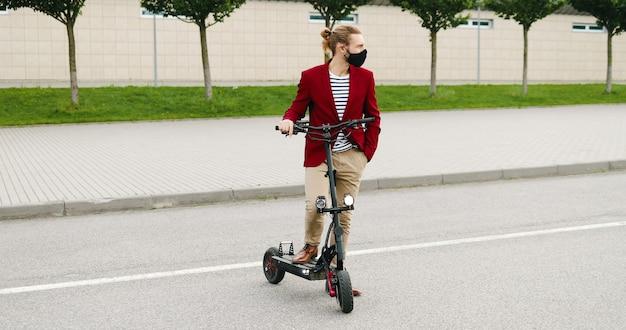 Retrato de joven guapo caucásico en chaqueta roja y máscara de pie al aire libre con scooter eléctrico. chico guapo con estilo en el vehículo en las calles de la ciudad. tiro de carro. acercándonos. concepto de pandemia.