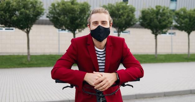 Retrato de joven guapo caucásico en máscara de pie al aire libre, apoyado en bicicleta o scooter eléctrico y sonriendo a la cámara. hombre guapo con estilo posando para la cámara en bicicleta. concepto de pandemia.