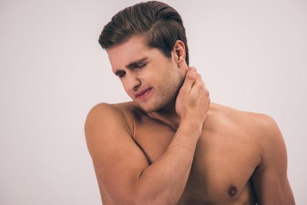 Retrato de joven guapo desnudo sintiendo dolor
