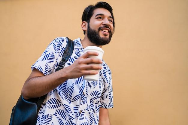 Retrato de joven guapo disfrutando del verano, vistiendo ropa de verano y bebiendo algo.