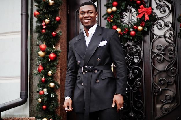 Retrato de joven y guapo empresario afroamericano en traje cerca de decoraciones para árboles de año nuevo con corona en la puerta.