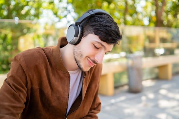 Retrato de joven guapo escuchando música con auriculares mientras está sentado al aire libre. concepto urbano.