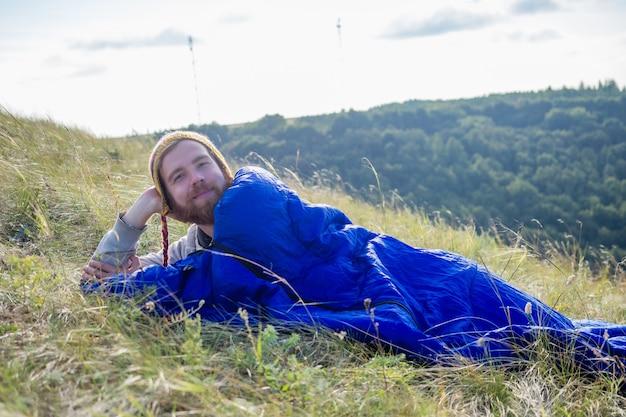 Retrato de un joven guapo excursionista pelirrojo barba hombre en un divertido sombrero de yak de lana tejido de nepal en la naturaleza acostado en un saco de dormir azul paisaje lago y colinas