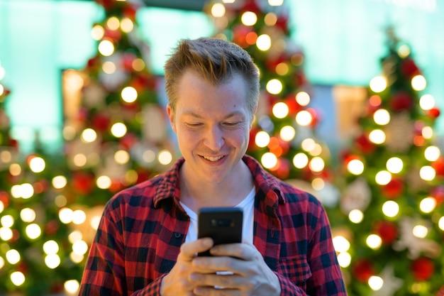Retrato de joven guapo hipster en árboles de navidad iluminados al aire libre
