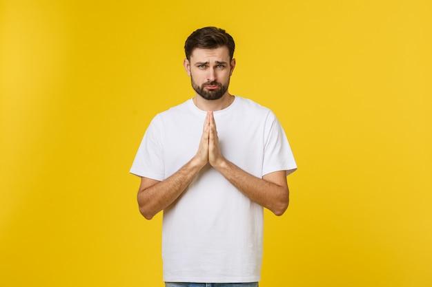 Retrato de joven guapo manteniendo las manos cruzadas y mirando pensativo