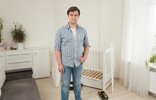 Retrato de joven guapo posando contra la cuna desmontada en la guardería