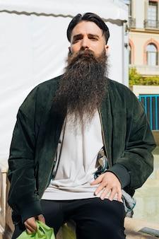 Retrato de joven guapo sentado en la barandilla mirando a cámara
